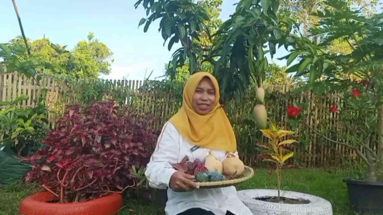 Khairin Dahlan atau akrab disapa Nanik, berfoto dengan hasil panen di kebun miliknya, yang terinspirasi dari tayangan Bumiku Satu DAAI TV (Dok. Pribadi).